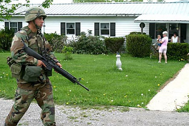 A soldier patrols what appears to be an American neighborhood.